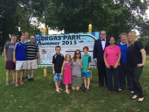 Friends of Gorgas Park, and park volunteers from City Light Church join East River Bank President Christopher McGill and employees and volunteers from the bank in front of the 2015 Concert and Movie Series Sign.